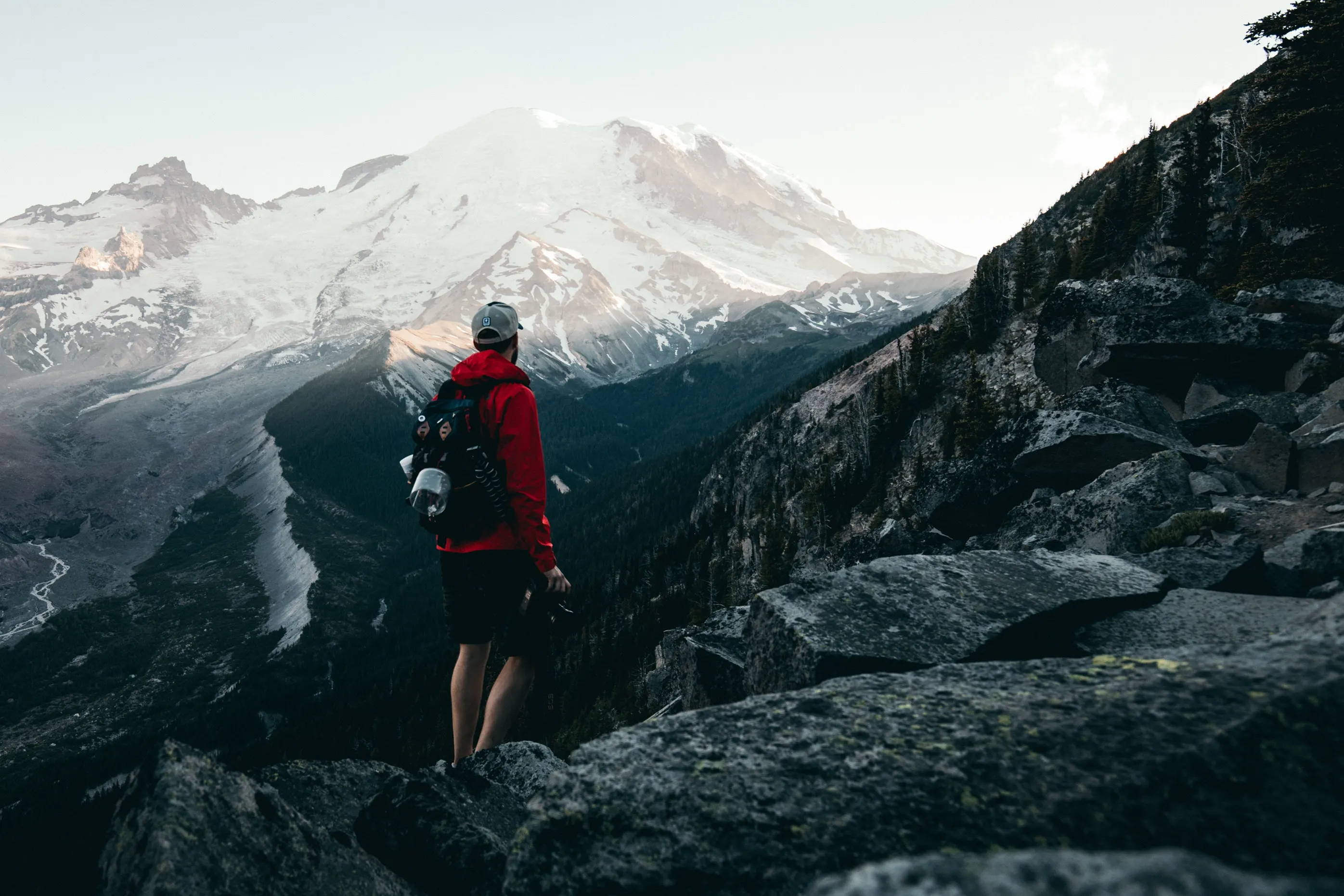 Easy Day Trips from Seattle, Washington: Man with bright red jacket wearing backpack and hat looking off into the distance at Mt. Rainier.