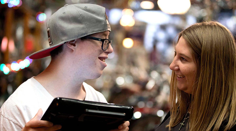 Ein junger Mann erhält Tipps von einer Logopädin, um sein UK-Gerät besser nutzen zu können