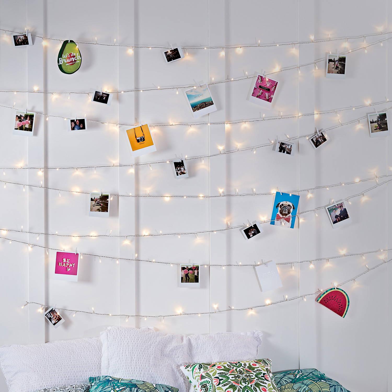 Lichterkette warmweiß mit kleinen Fotos vor weißer Wand.