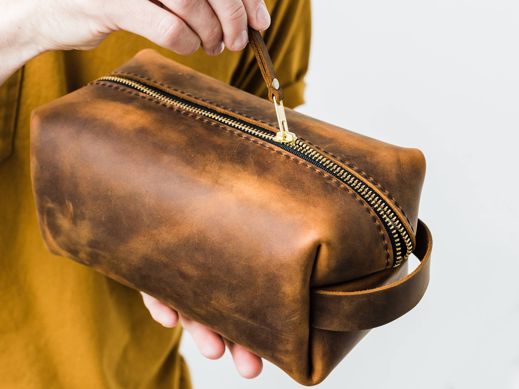 handmade leather dopp kit being unzipped
