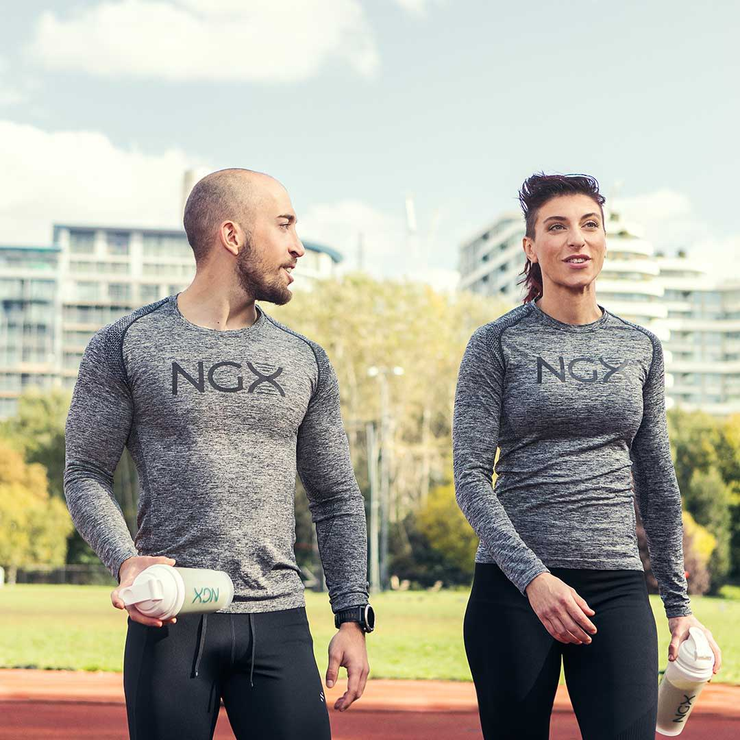 White man and woman in performance clothing holding NGX shaker.