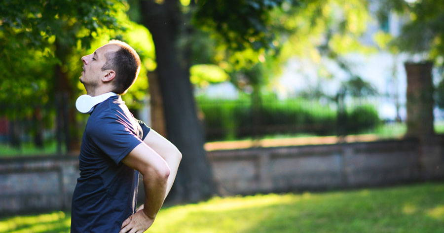 man holding back in park