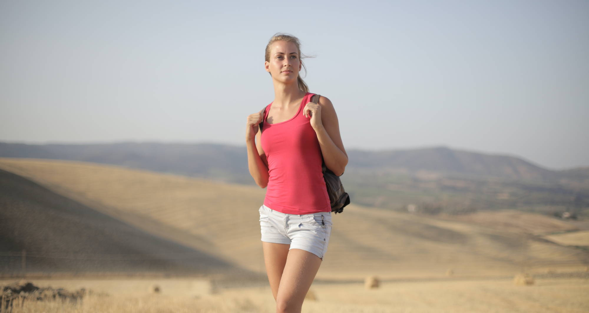 A woman stands in one of the best hemp tank tops available today in an empty field.