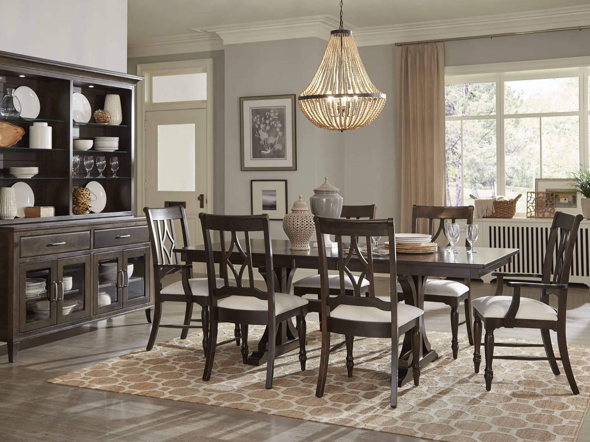 wood dining chairs around matching table in front of large china cabinet