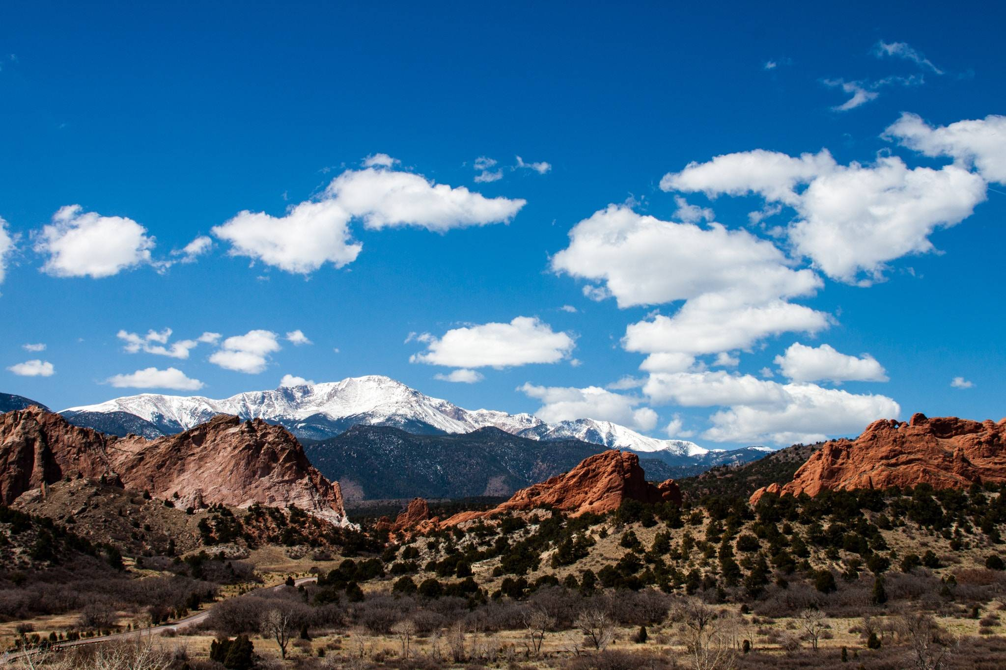 Things to do in Colorado: Snow-capped rocky mountains in distance with reddish rock in foreground in Colorado.