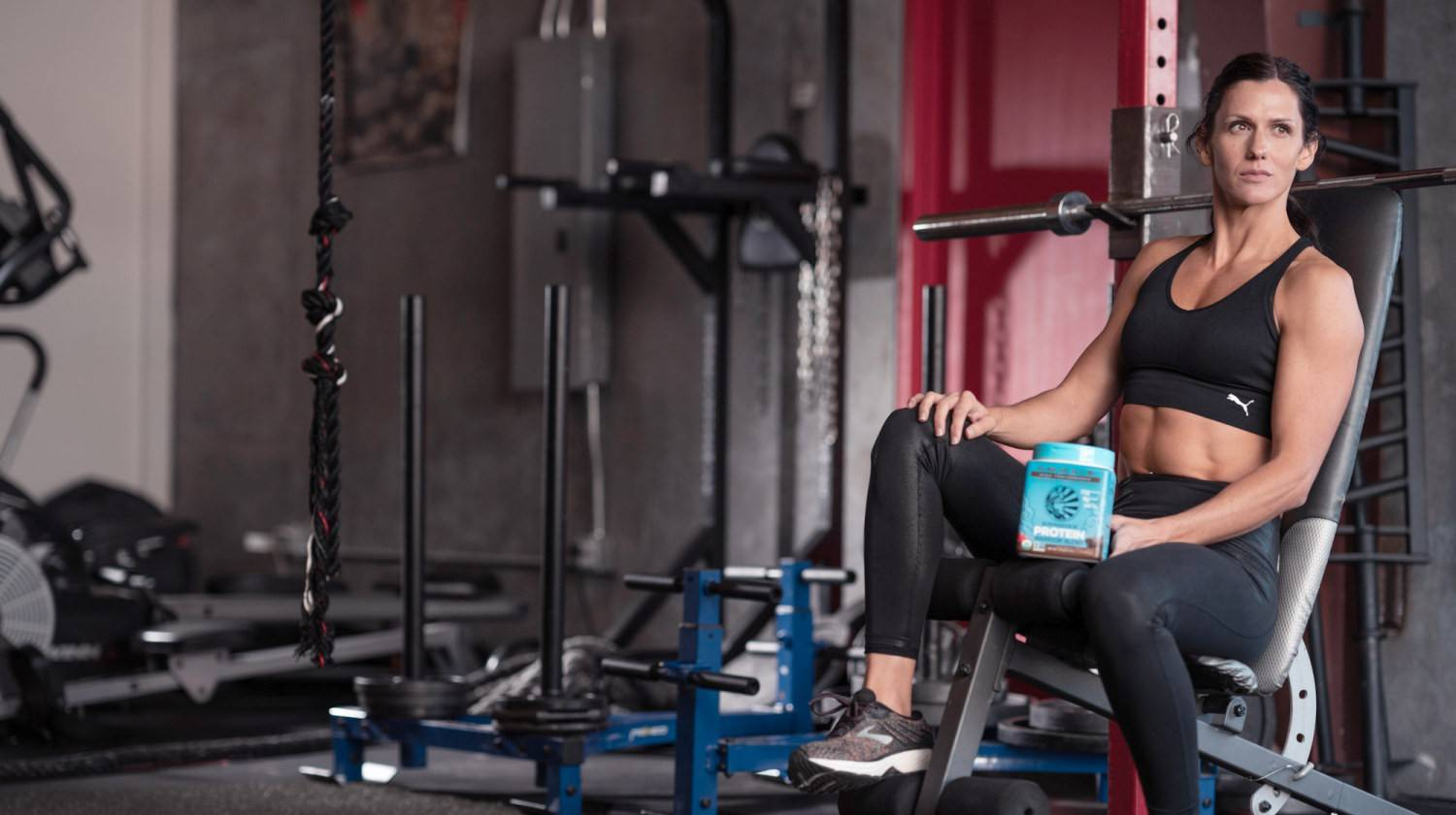 Ralani holding Warrior blend protein powder sitting at the gym   The Best Protein Powder for Women   protein powder for women   Featured