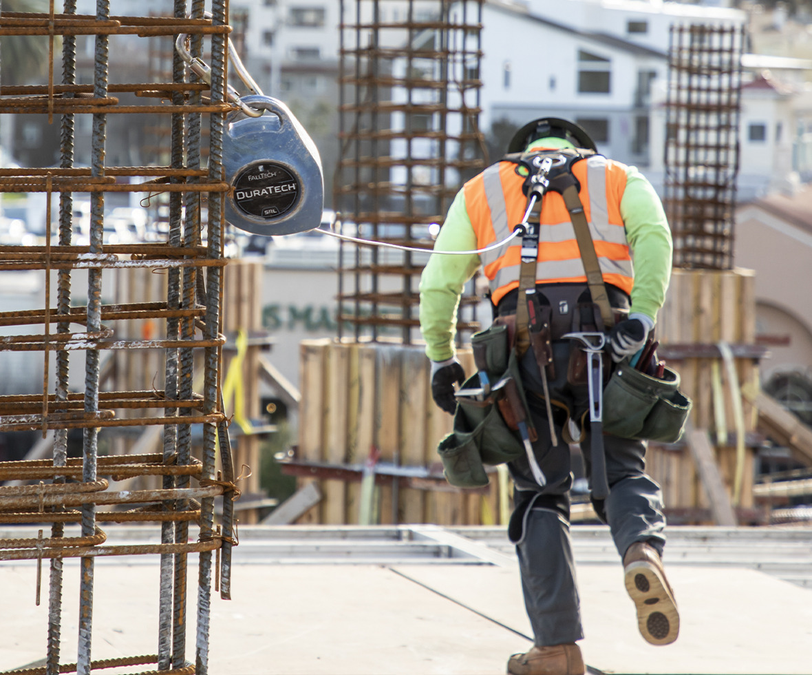 Construction worker walking away connected to a DuraTech self-retracting lifeline block anchored to rebar