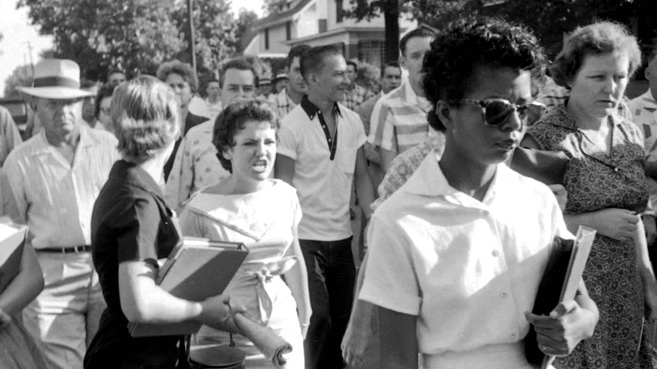 An African American student carrying her school books into a newly integrated school in 1957