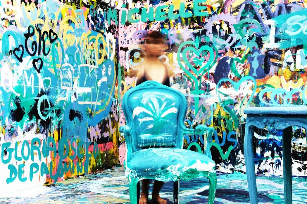 A girl standing behind a chair in a room full of oil art