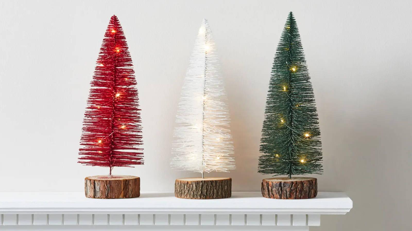 Trio of mini Christmas trees sat on mantel