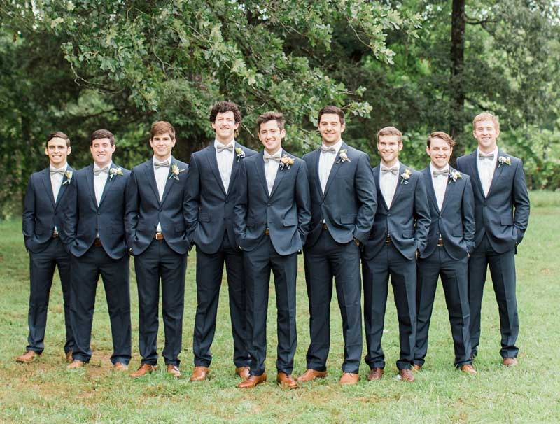 Groomsmen wearing matching mint green bow ties, gray suits and brown oxfords