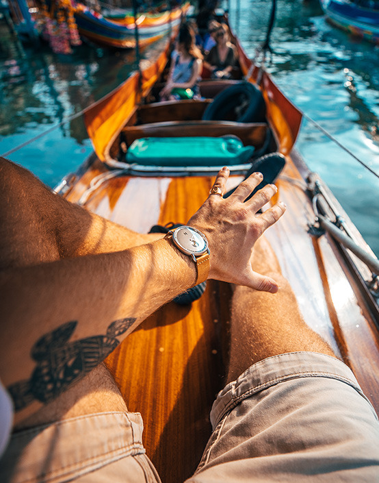 first person wrist shot of man in river boat