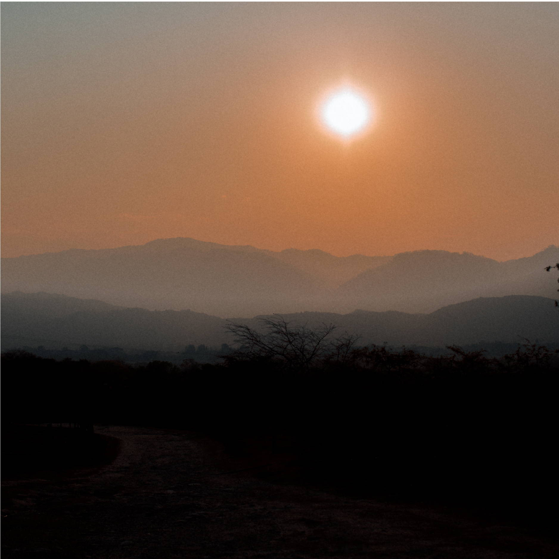 The sun sets over the silhouetted Zamarano Valley Mountains in Honduras.