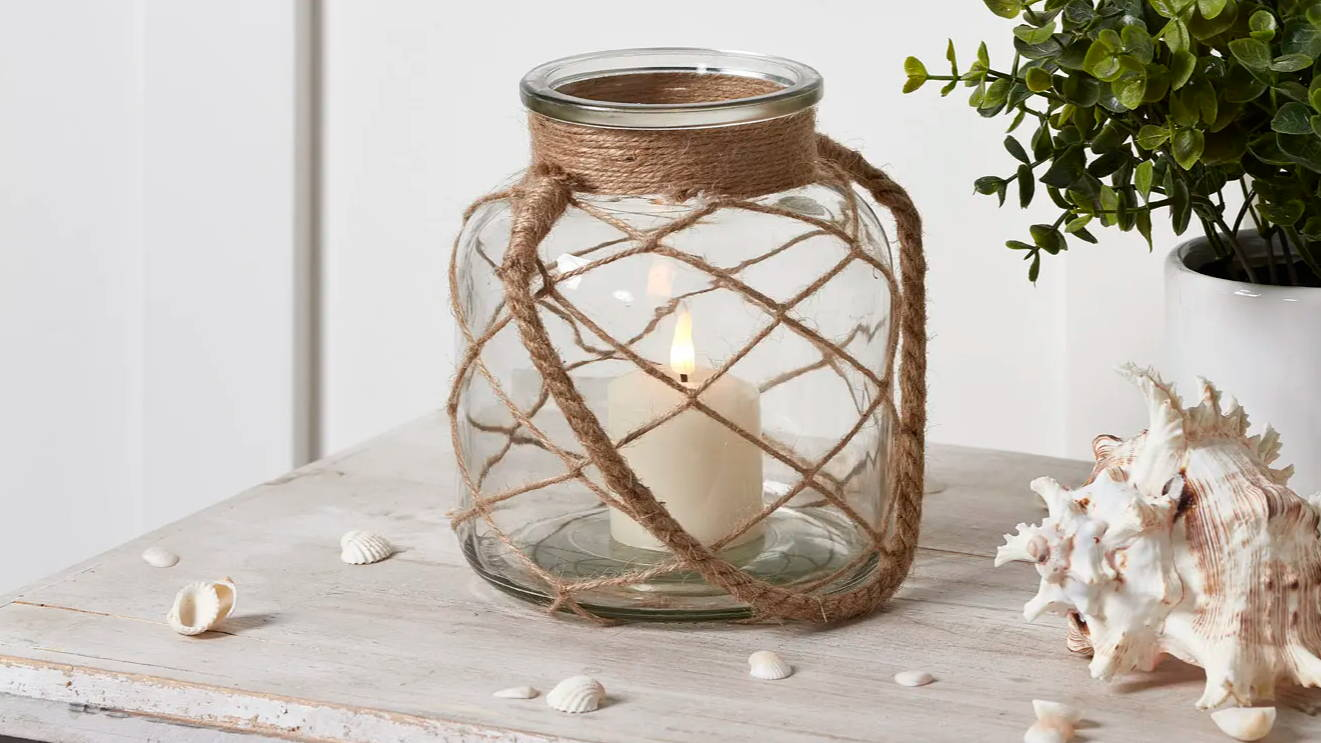 Glass lantern on coastal table top with TruGlow candle illuminated within it