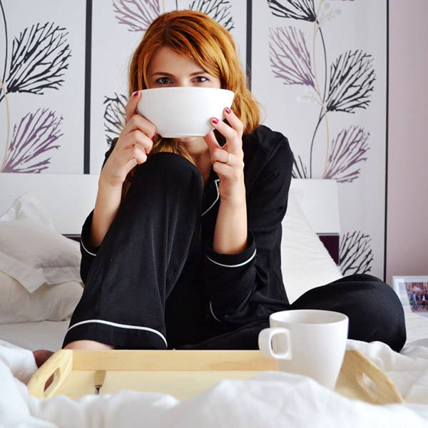 Woman sitting in bed smiling and having breakfast
