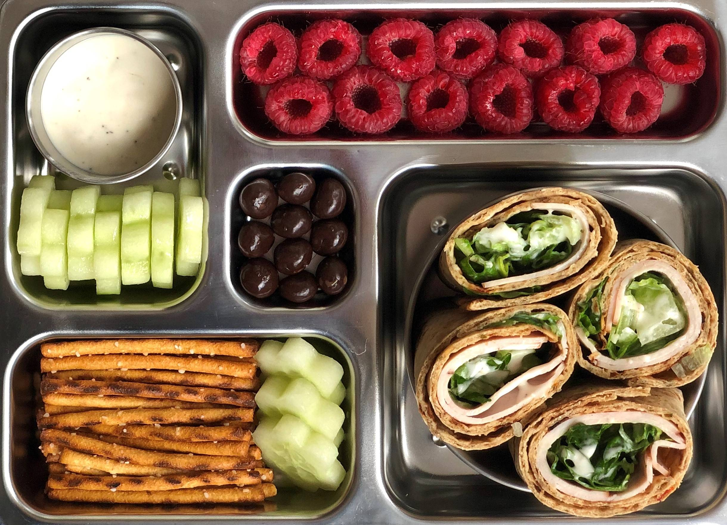 Sneak peek of a kid's quick and healthy school lunch containing Turkey Caesar Lavash Rollup, pretzel sticks, cucumber cutouts with dip, raspberries, and dark chocolate covered dried fruit.