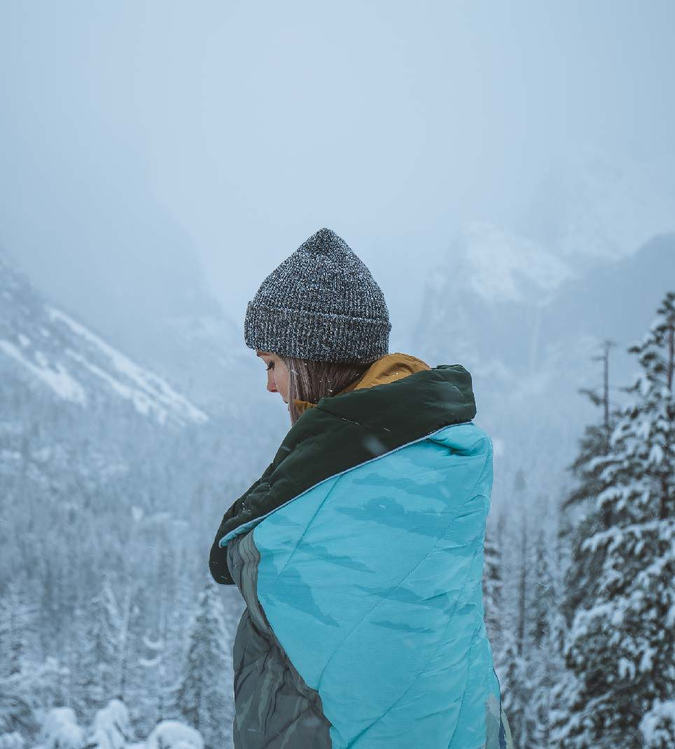 girl wrapped up in Original Puffy blanket Yosemite design