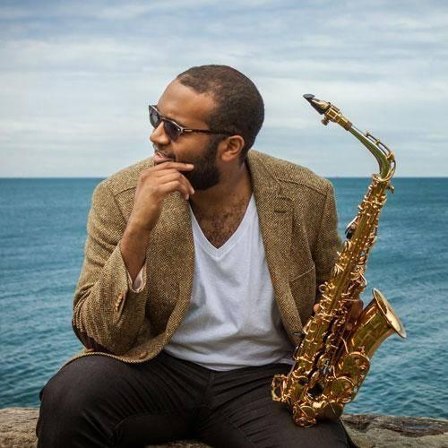 Sax player Rajiv Halim holding an alto sax