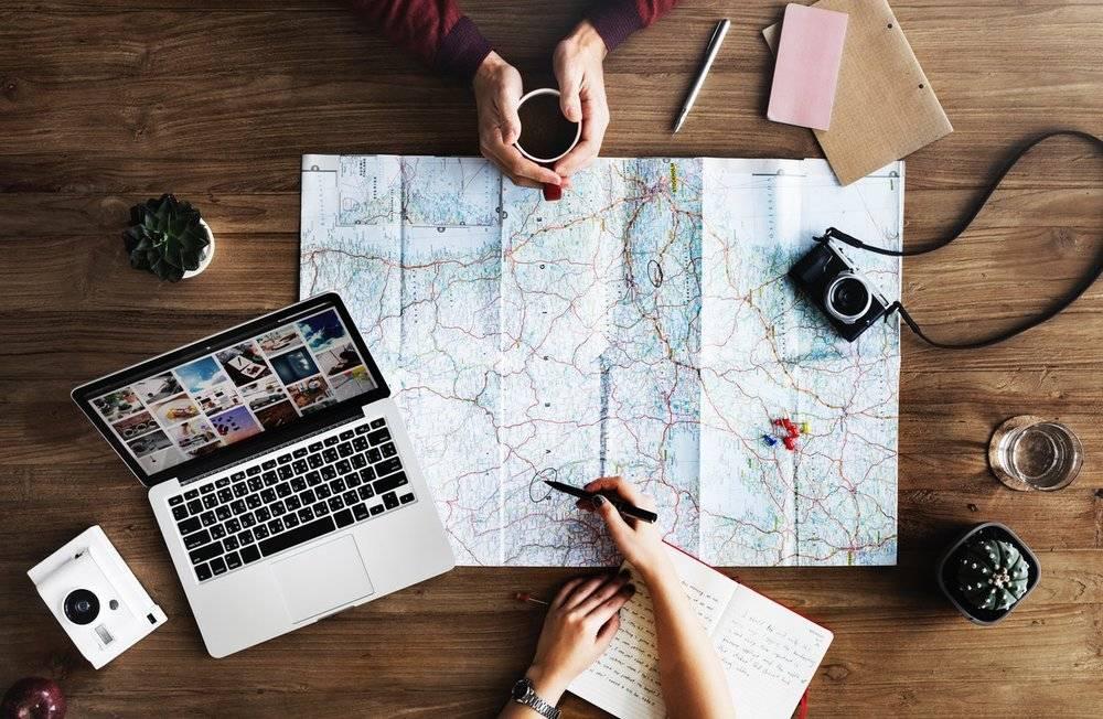 Map, laptop, cameras, journal.