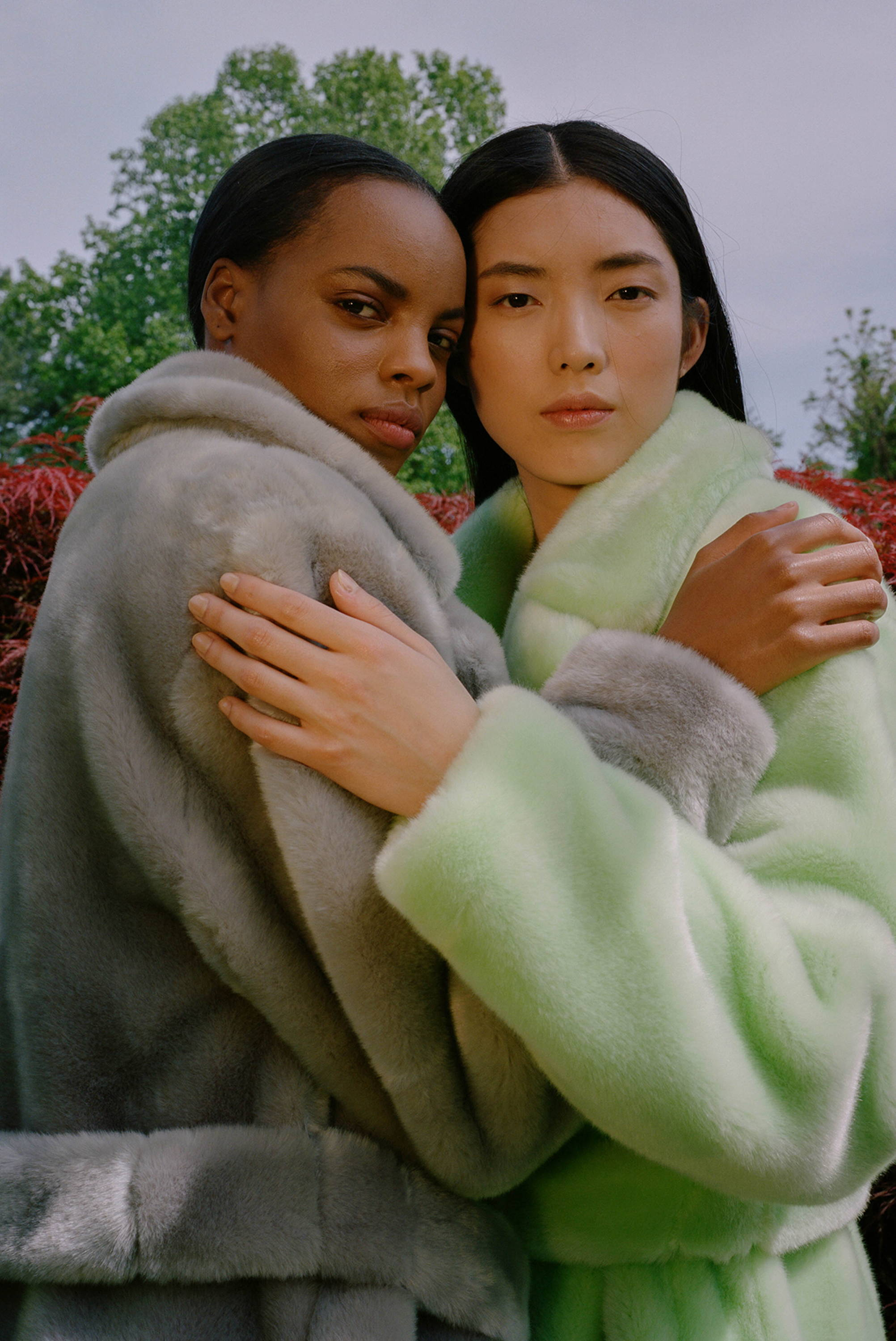 Two models hugging in the luxe faux fur oversized trench.