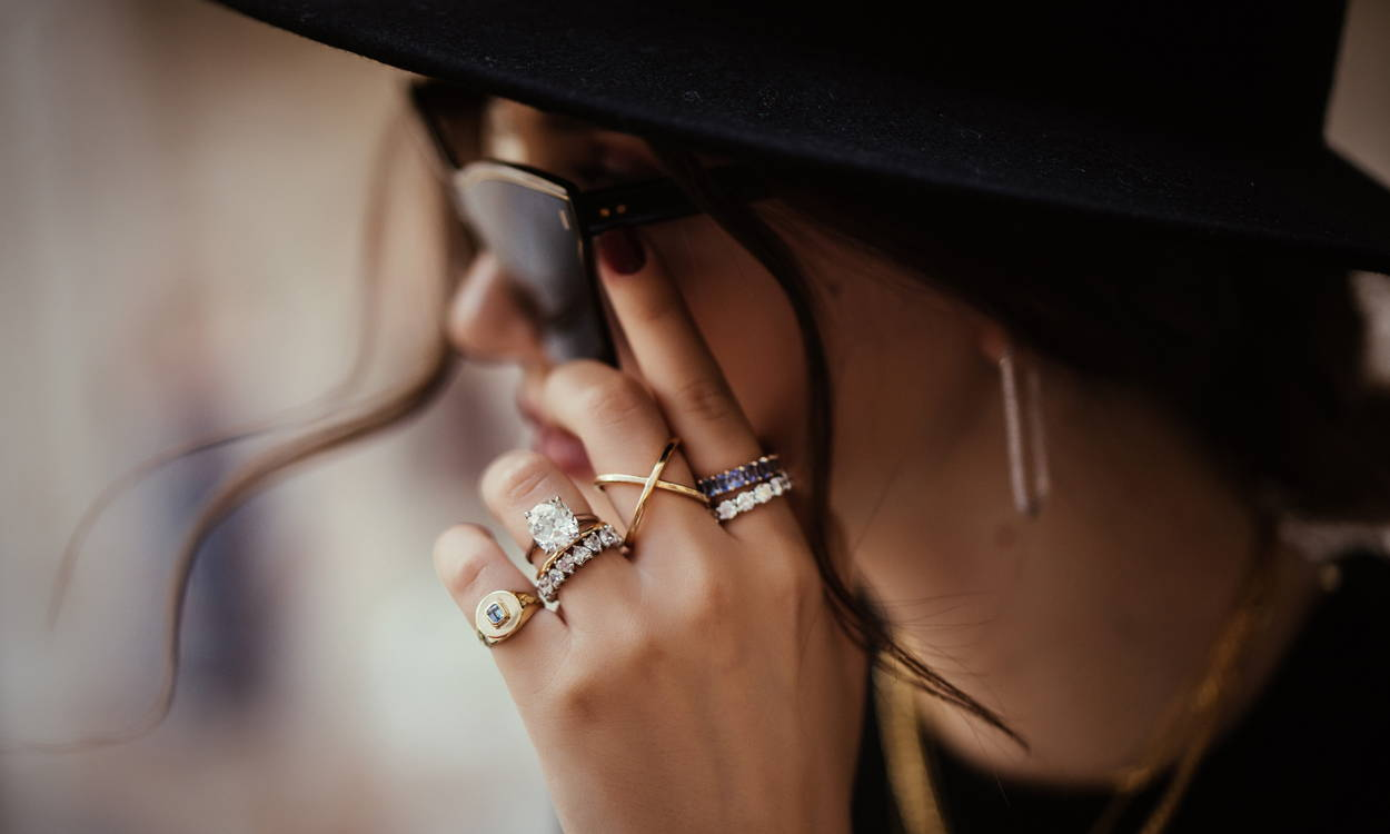 Model adjusting sunglasses wearing Ring Concierge fine jewelry