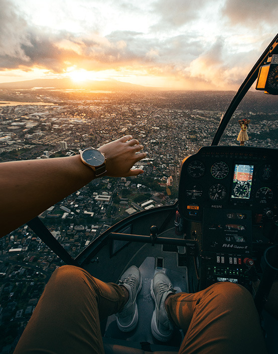first person view wrist shot from man in helicopter over city