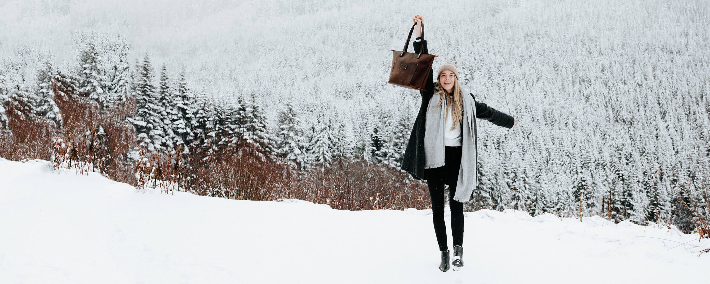smiling woman holding handmade leather tote bag by portland leather goods in a snowy field