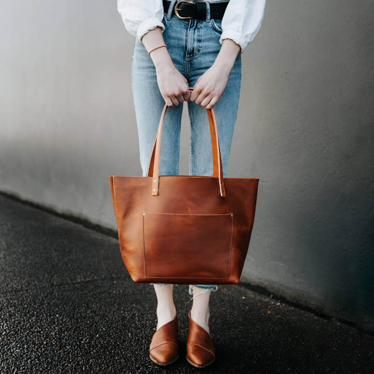 a girl holding a leather tote in front of her legs