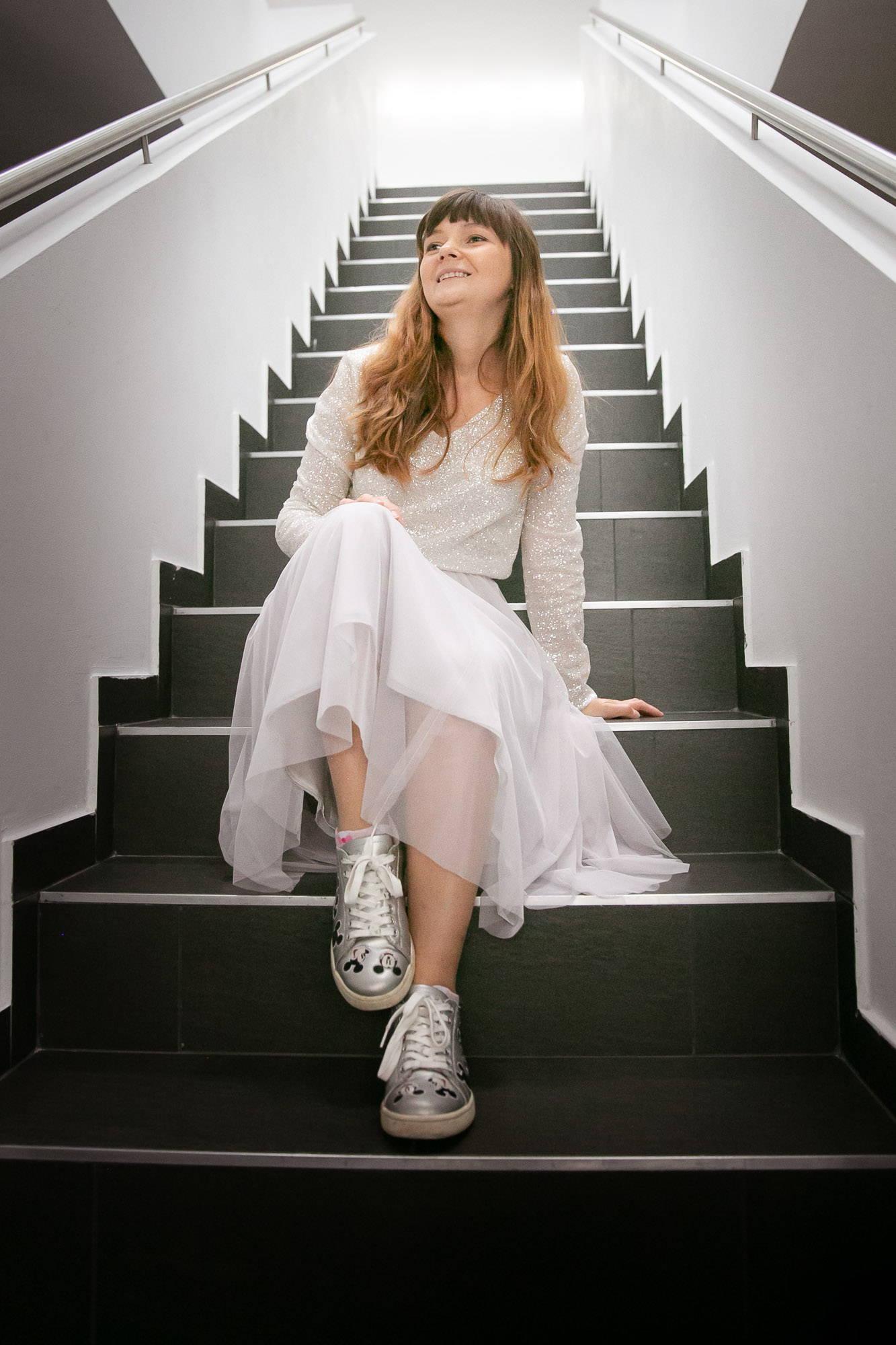 noni Brautmode, Hochzeitskleid, zweiteilig, mit Glitzer-Top und kurzem Softtüllrock in Pastellviolett, kombiniert mit silbernen Sneakern
