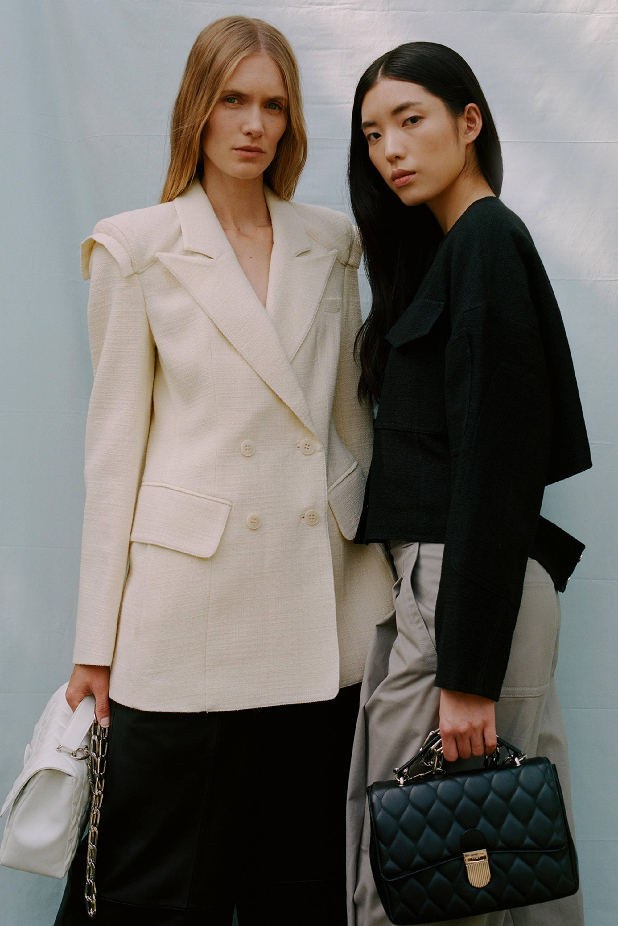 Two models wearing basketweave group. One model is wearing the white blazer. The other a black jacket.