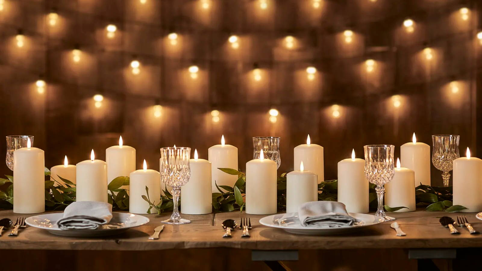 TruGlow pillar candles illuminated as part of table centrepiece with foliage distributed in and around them