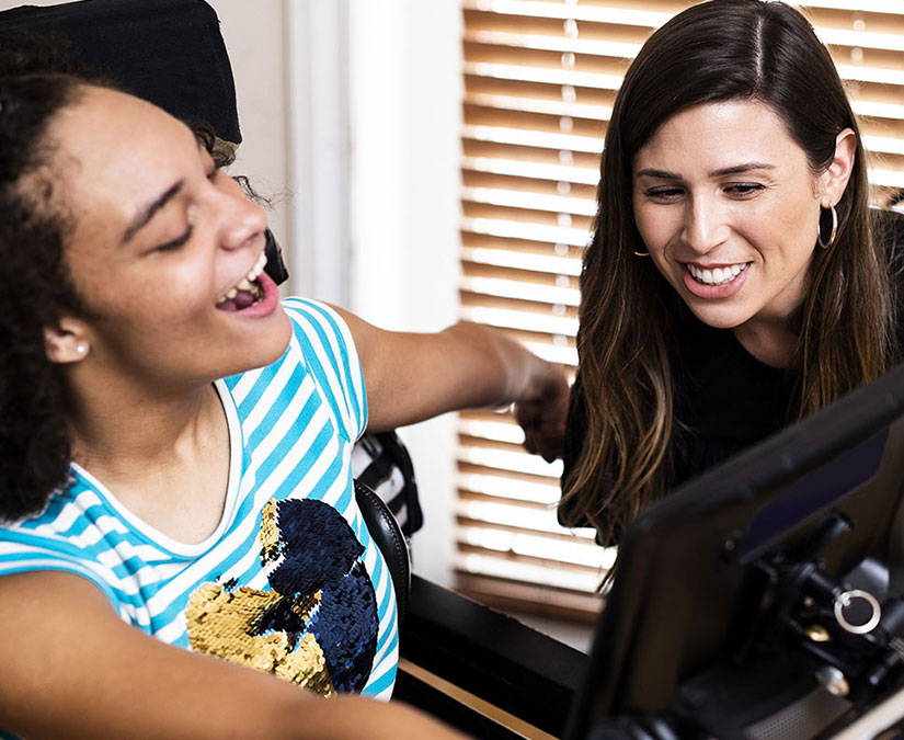 Young woman using a Tobii Dynavox I-Series device with her caregiver