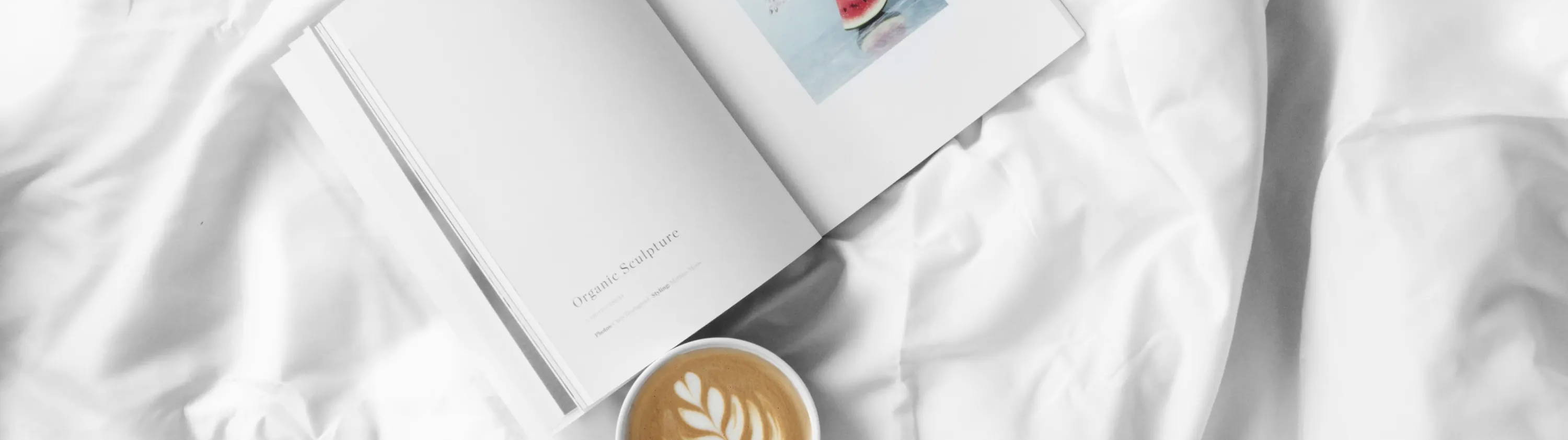 An open book with cup of latte on white eucalyptus bed sheets