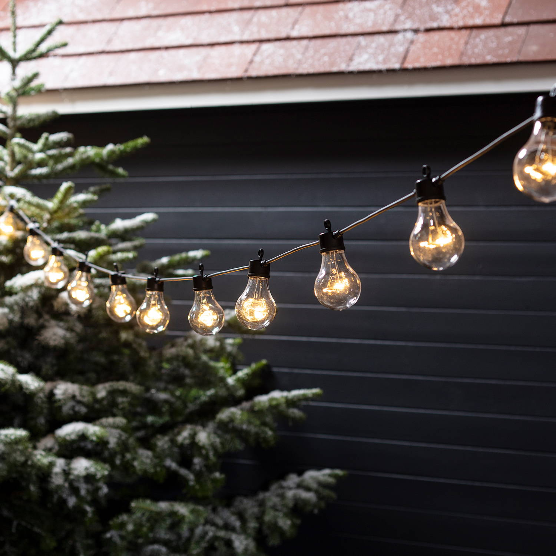 Festoon lights hung outside in a snowy setting