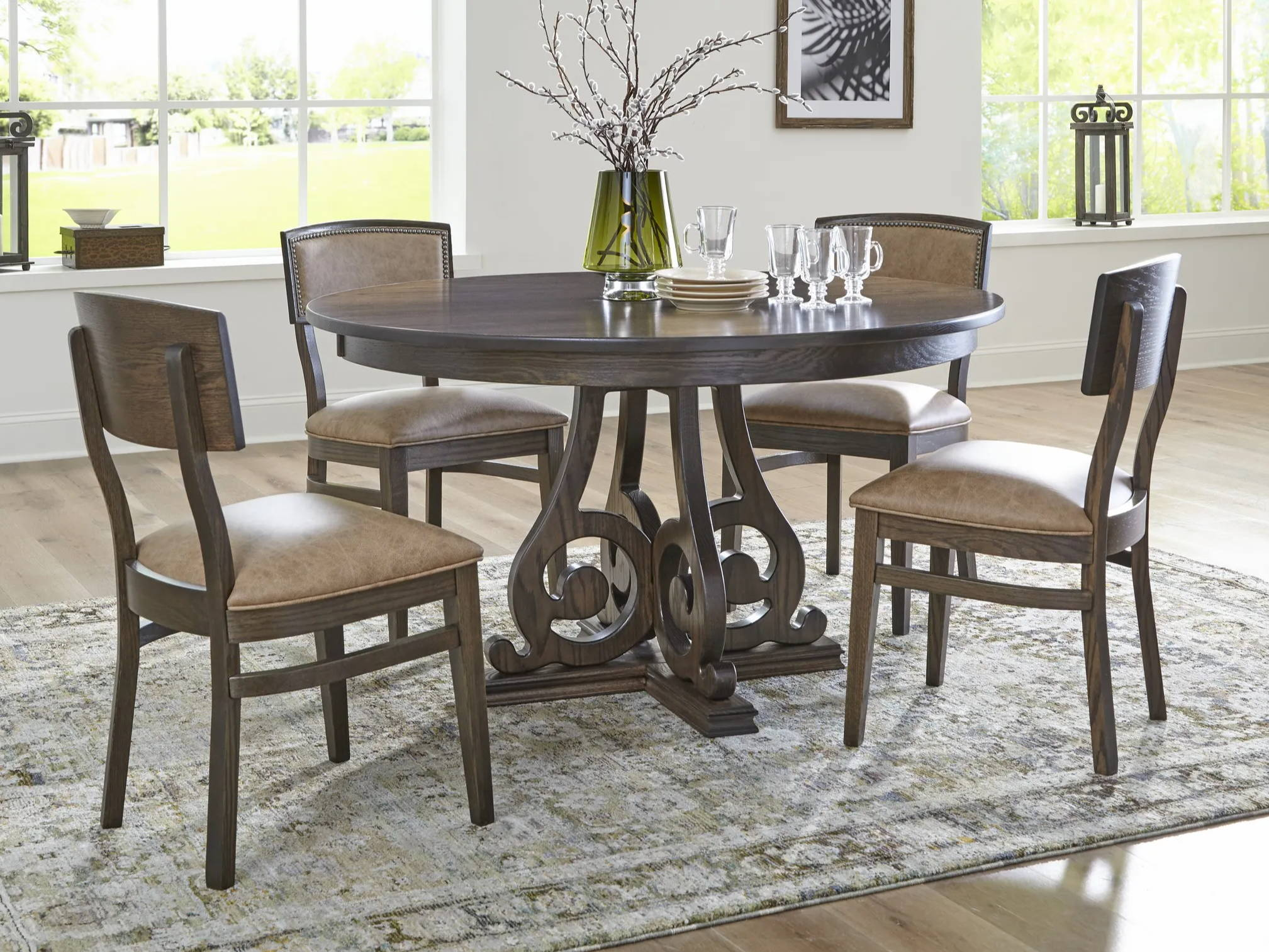 four wood chairs with upholstered seats around a round dining table