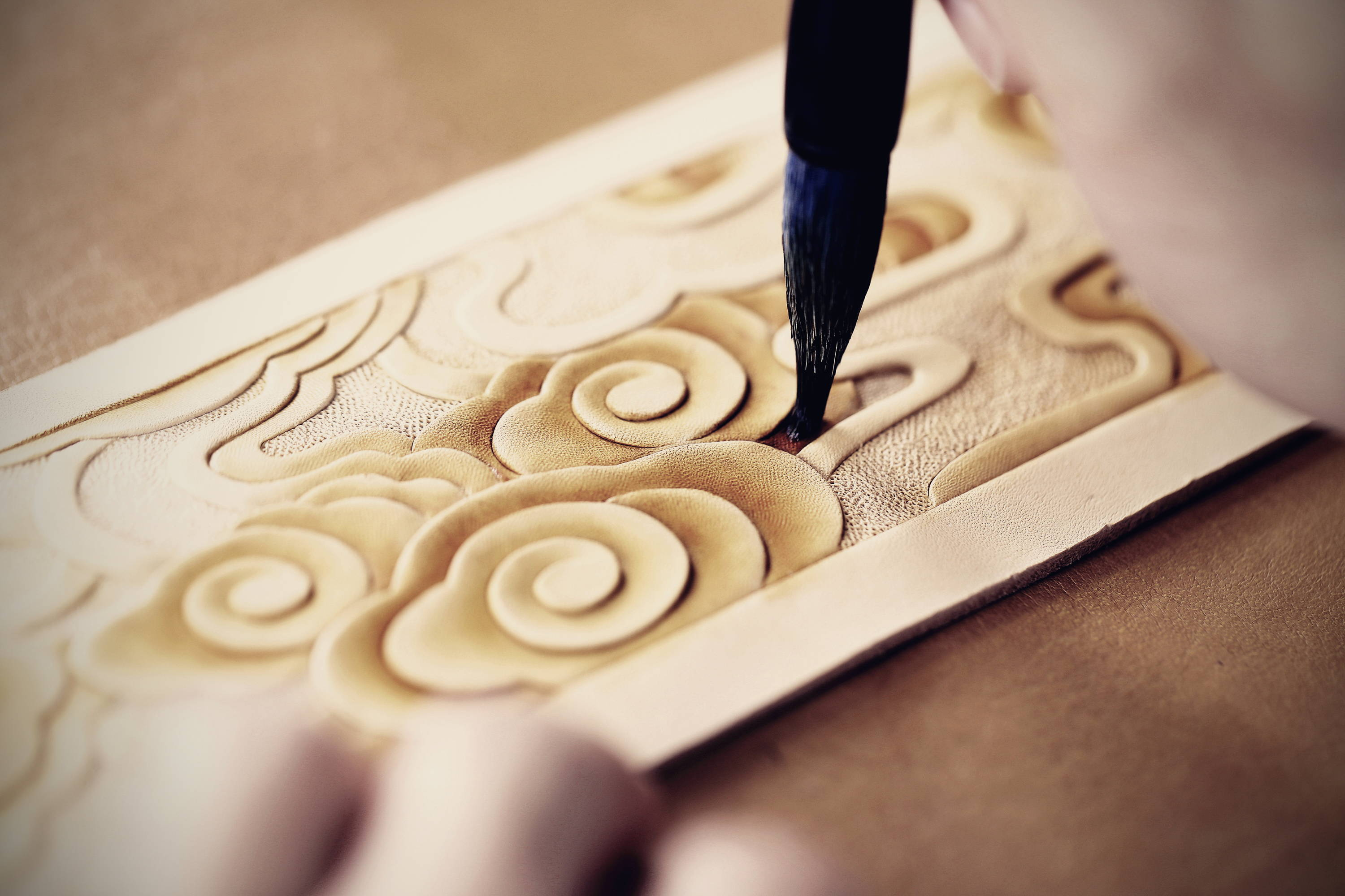 a craftsman is hand painting on the leather