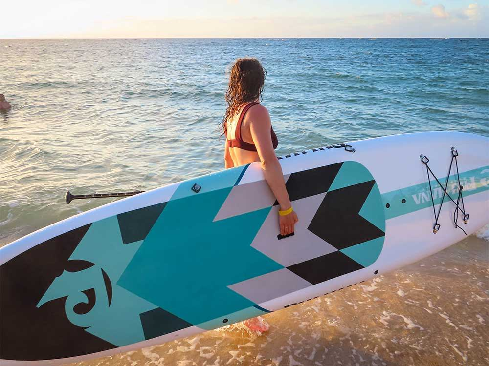 Girl carrying the Big EZ Hawaiian stand up paddle board along the beach