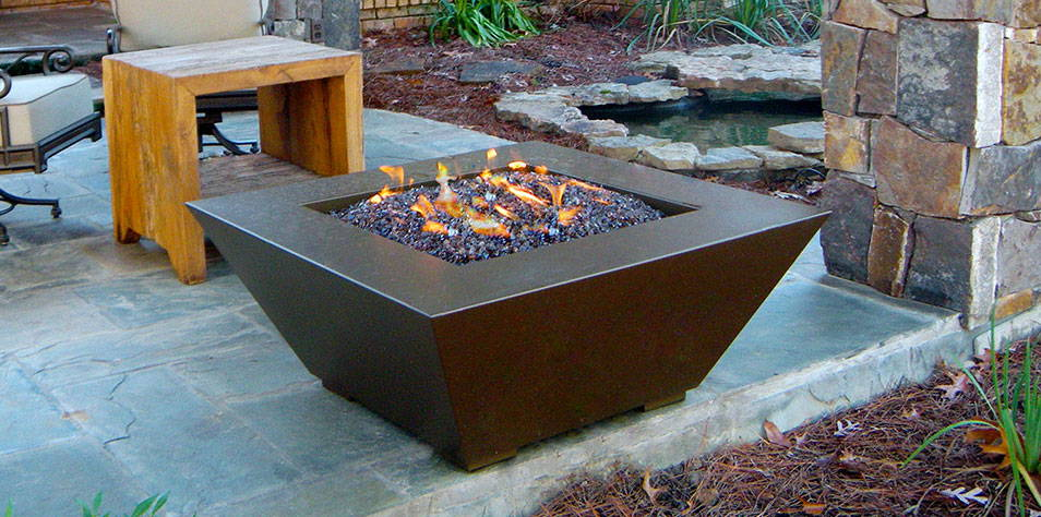 A Mill series fire pit is ignited on a stone patio