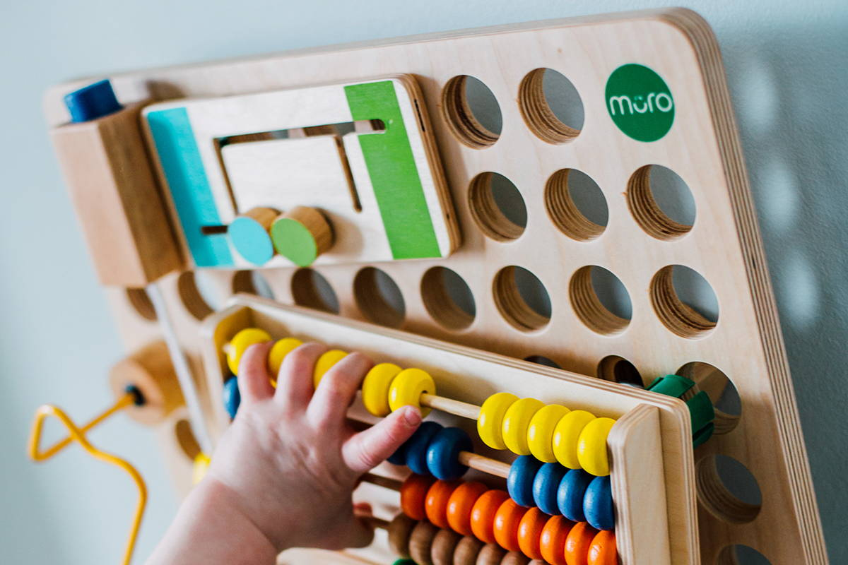 A child placing an abacus on to the muro busy board