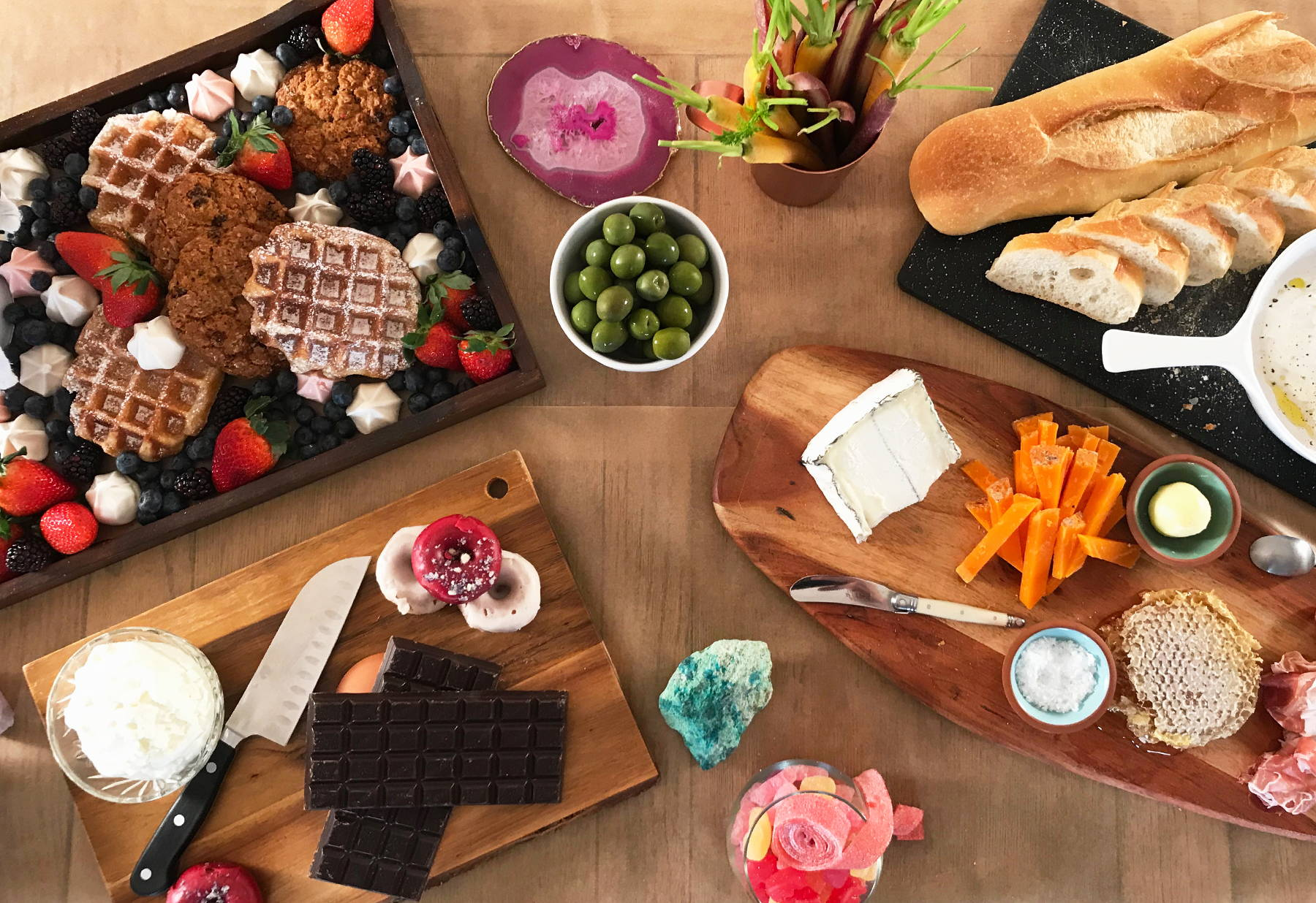 Unicorn Snot's Galentine's Day snack spread has cheeses, meats, waffles, olives, cookies, donuts, and chocolate.