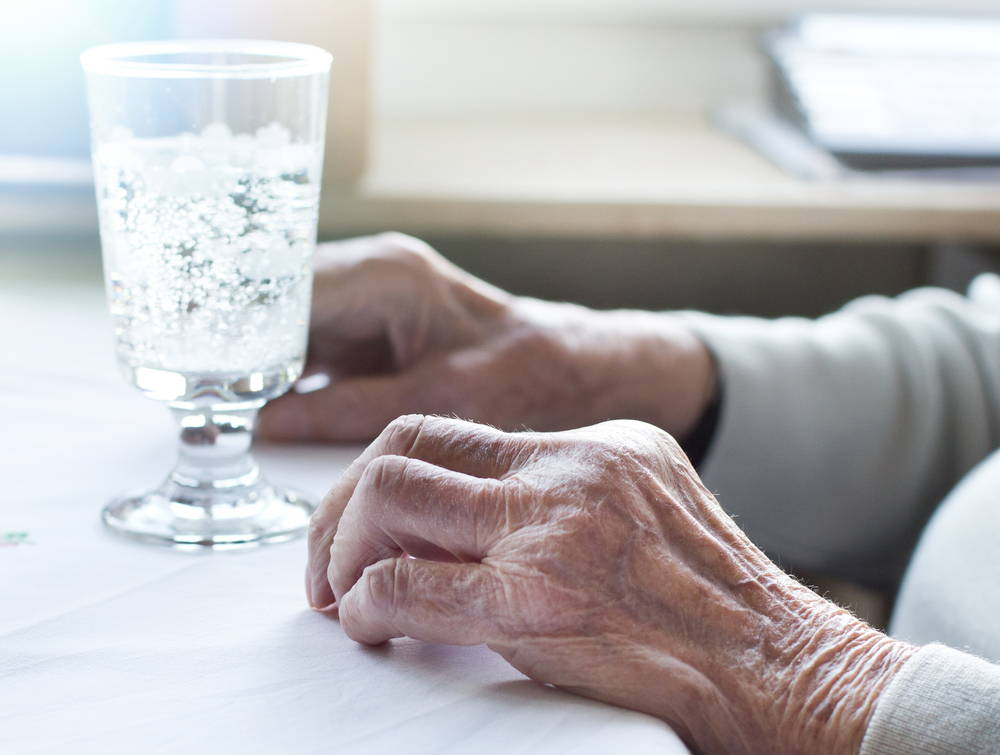 Elderly person's hands sit next to a glass of water