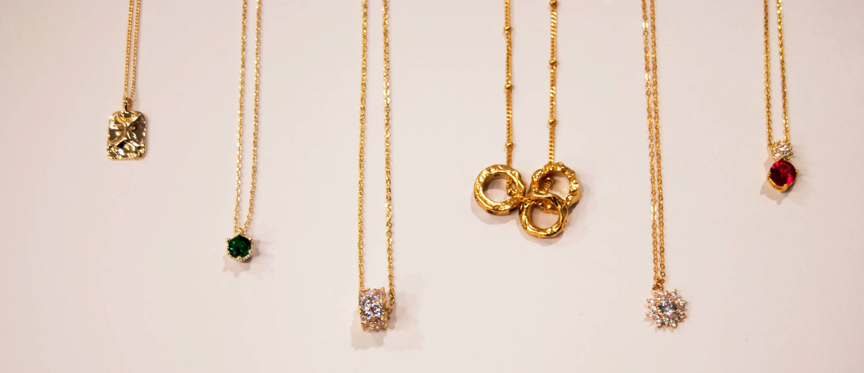 diamond, gemstone, and gold necklaces hanging at moi accessories