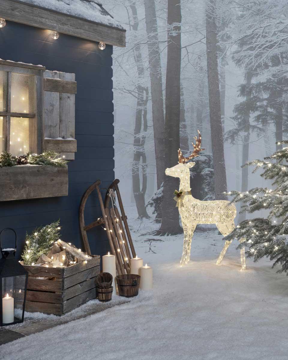 LED Rentier im Schnee zwischen einer beleuchteten Holzhütte und einem beleuchteten Tannenbaum