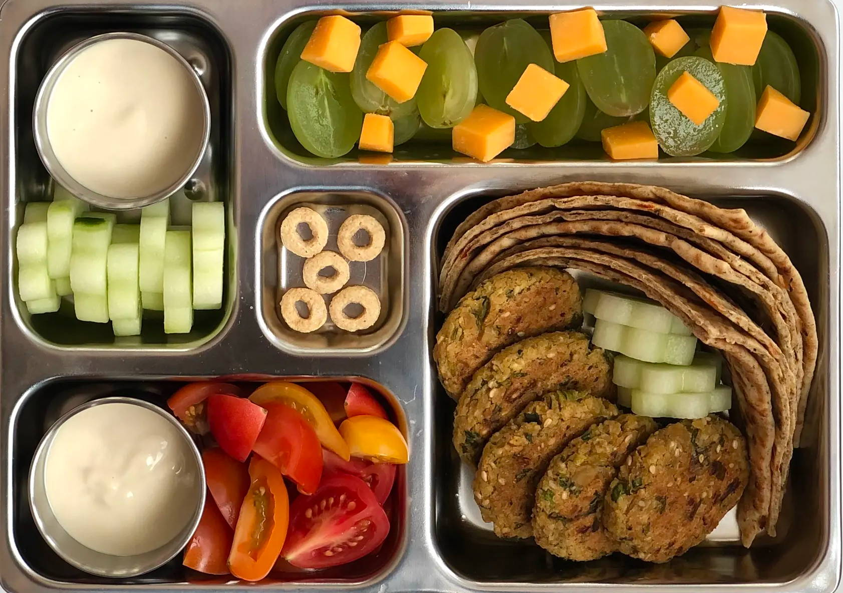 Sneak peek of a kid's quick and healthy school lunch containing Falafel Dipper, Tahini Drizzle Sauce,  English Cucumber Cut-Outs, Rainbow Cherry Tomatoes, Lavash Wedges,  Grapes & Cheddar, and Whole Grain O's.