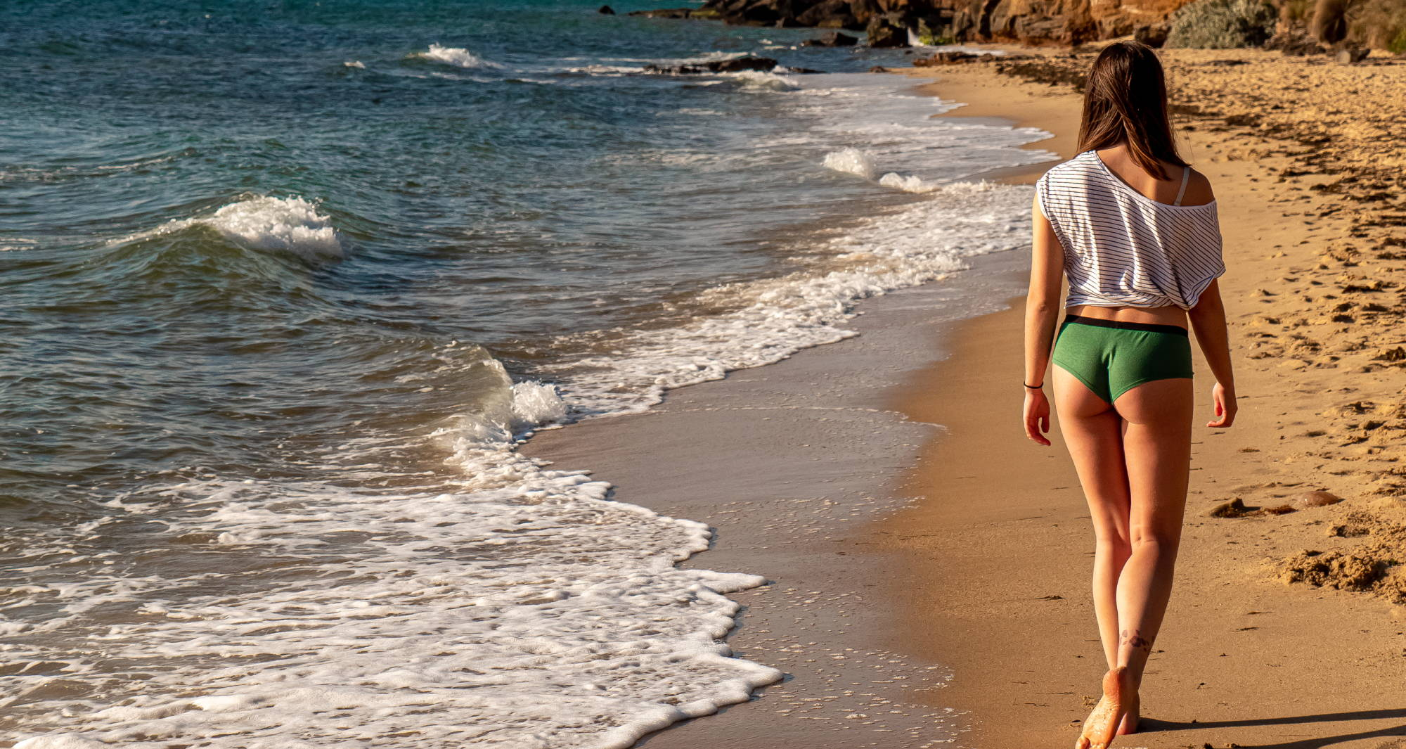 A woman wearing upf fabric underwear while walking down the shore of a beach.