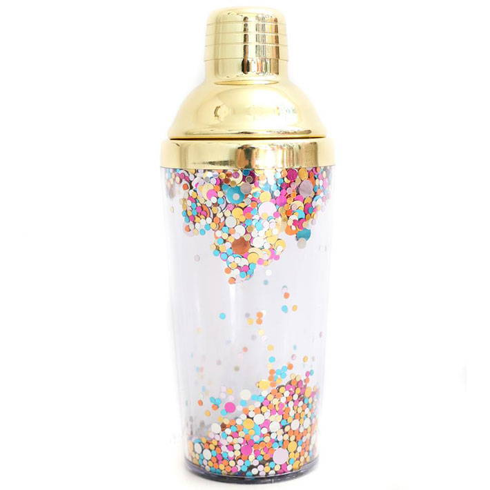 A cocktail shaker with confetti in the lining and a gold topper.