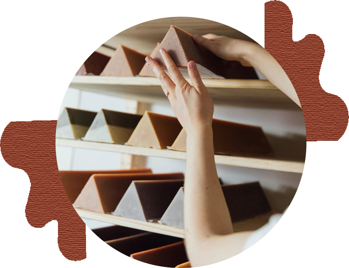 circular photo of wild lather triangular soaps on wood shelves surrounded by abstract brown shapes