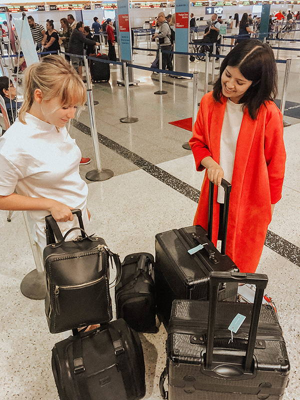 Shelby Taylor with her CALPAK Kaya Laptop Backpack in Black and CALPAK Murphie Under-Seat Carry-On in Black. Lillian Fahey with her CALPAK Trnk 2Pc. Luggage in Black and CALPAK Murphie Under-Seat Carry-On in Black.