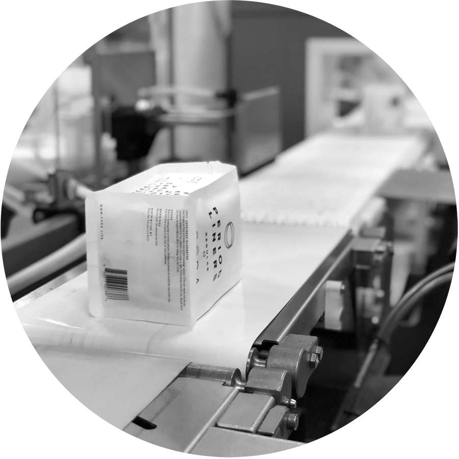 A package of Cora organic bladder liners sitting on a conveyor belt