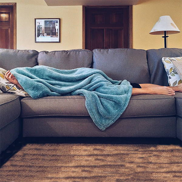 Woman hiding exhausted under a turquoise blanket on the couch